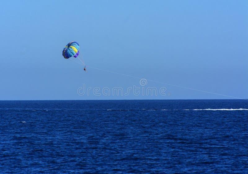 Láncese en paracaídas sobre el mar contra un cielo azul y una agua de mar clara, remolcando en un barco Montar un paracaídas detr fotos de archivo libres de regalías