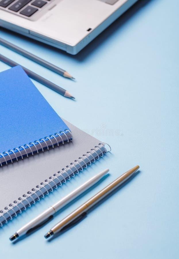 Lápices al lado de los cuadernos y plumas en un fondo azul foto de archivo libre de regalías