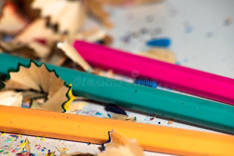 Lápices azules, anaranjados y rosados entre virutas fotos de archivo