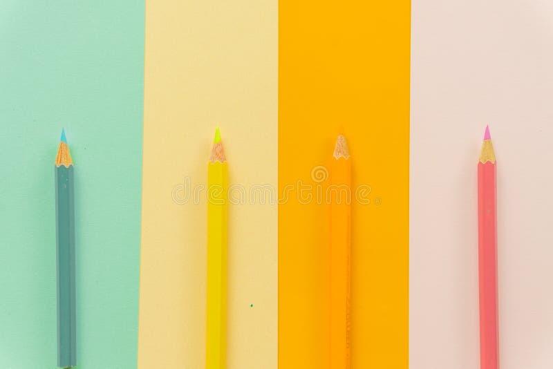 Lápices coloreados azules, amarillos, naranja y rosa en fondo azul, amarillo, anaranjado y rosado imagen de archivo