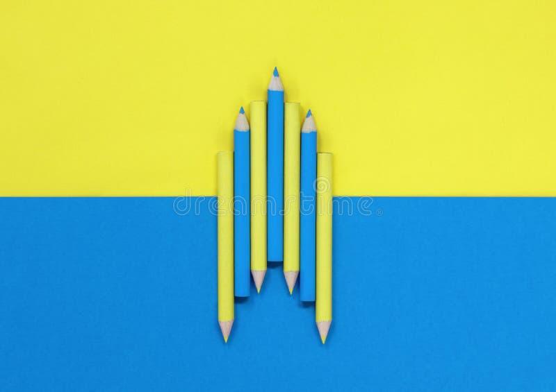 Lápices coloreados azules y amarillos, en un fondo azul y amarillo foto de archivo