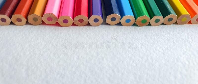 Lápices coloreados de madera, estilo del arco iris, en la hoja blanca del papel de dibujo con textura específica Copie el espacio foto de archivo