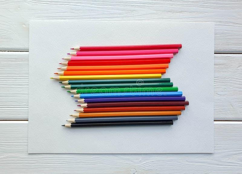 Lápices coloreados de madera, estilo del arco iris, en la hoja del papel de dibujo con textura específica, y el fondo de madera b fotos de archivo libres de regalías