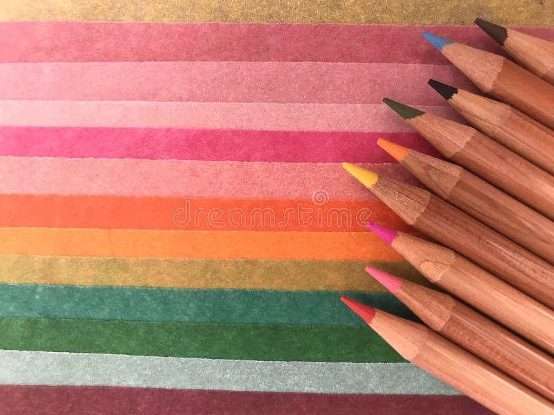 Lápices coloreados en las hojas del papel coloreado fotografía de archivo