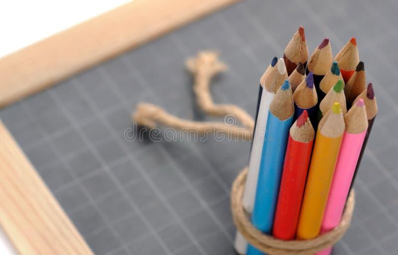 Lápices coloreados en pizarra fotografía de archivo libre de regalías
