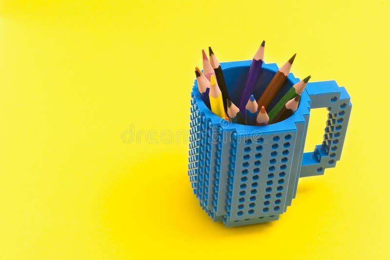 Lápices coloreados en un cubo en fondo amarillo De nuevo a concepto del scool imagenes de archivo