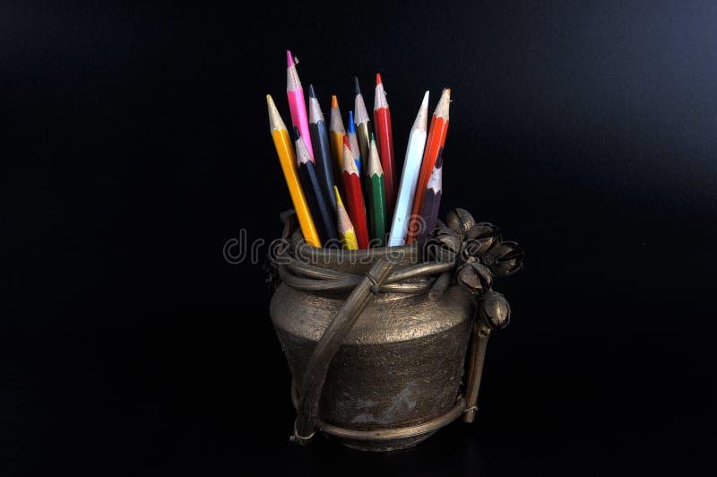 Lápices coloreados en un jarro de la arcilla fotografía de archivo libre de regalías