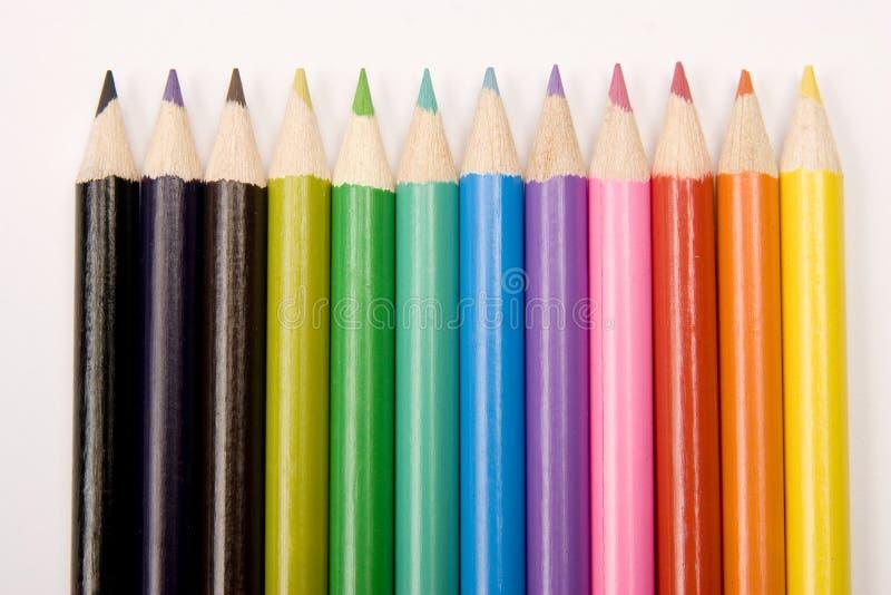 Lápices coloreados en una línea imágenes de archivo libres de regalías