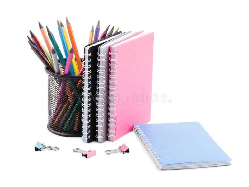 Lápices coloreados en una taza, los clips para los papeles y varios cuadernos de diversos colores fotos de archivo libres de regalías