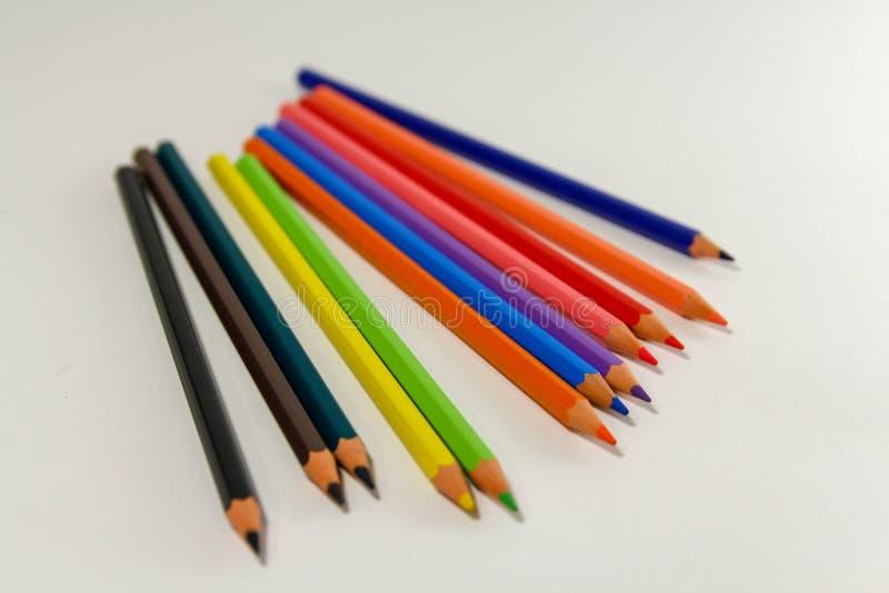 Lápices coloreados múltiples en un fondo blanco imagen de archivo