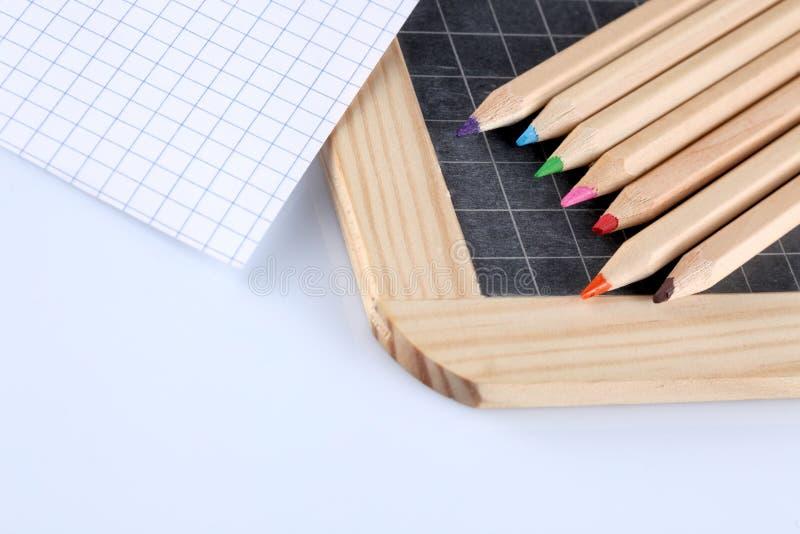 Lápices coloreados, pizarra de la tiza y una hoja de papel del papel del bloque aislada en el fondo blanco imagenes de archivo