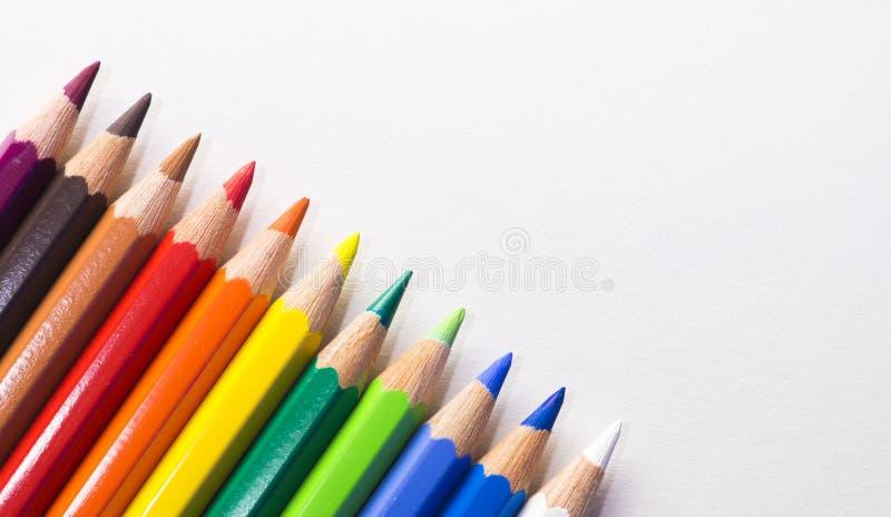 Lápices coloreados que ponen cuidadosamente en fila señalar hacia arriba a la derecha en un fondo blanco imágenes de archivo libres de regalías