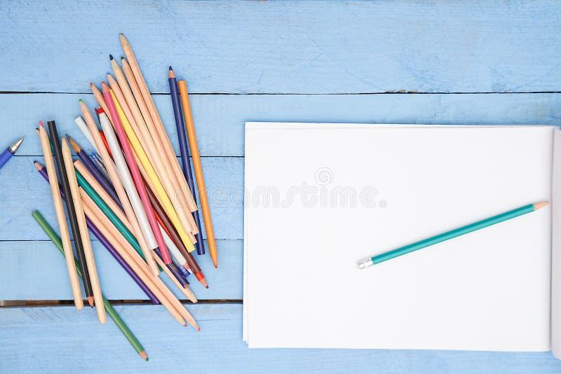 Lápices coloreados y un álbum con el espacio para el texto en un fondo de madera azul La visi?n desde la tapa imagenes de archivo