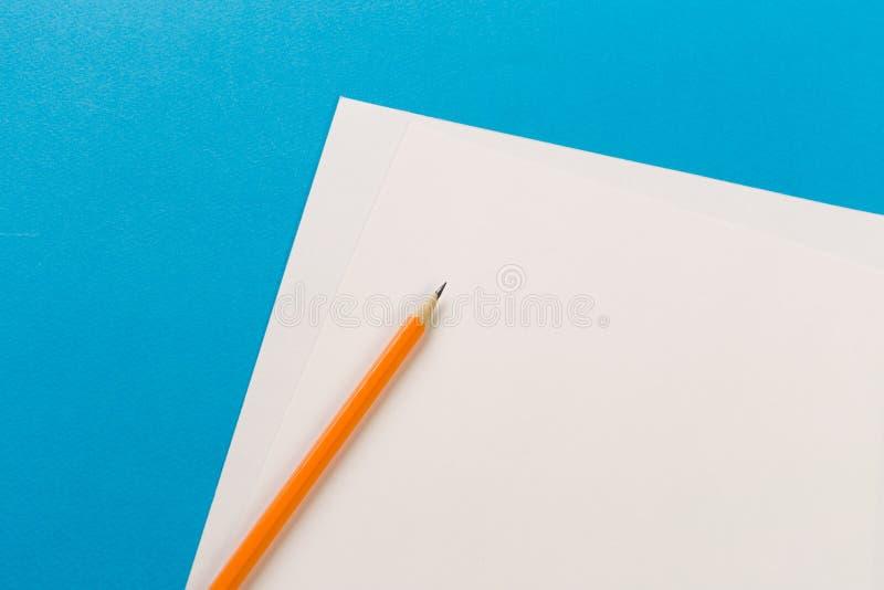 Lápices con las hojas del Libro Blanco en fondo coloreado foto de archivo libre de regalías