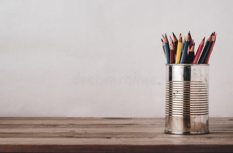 Lápices de dibujo coloreados en lata del metal en el escritorio de madera del tablón imagenes de archivo