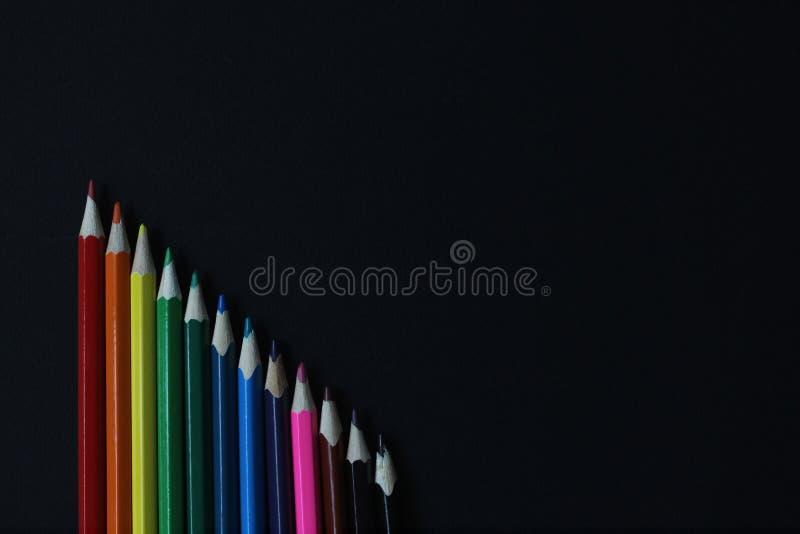 Lápices del color de la porción en fondo negro en fila, cierre de la visión superior para arriba Con el espacio para el texto De  foto de archivo libre de regalías