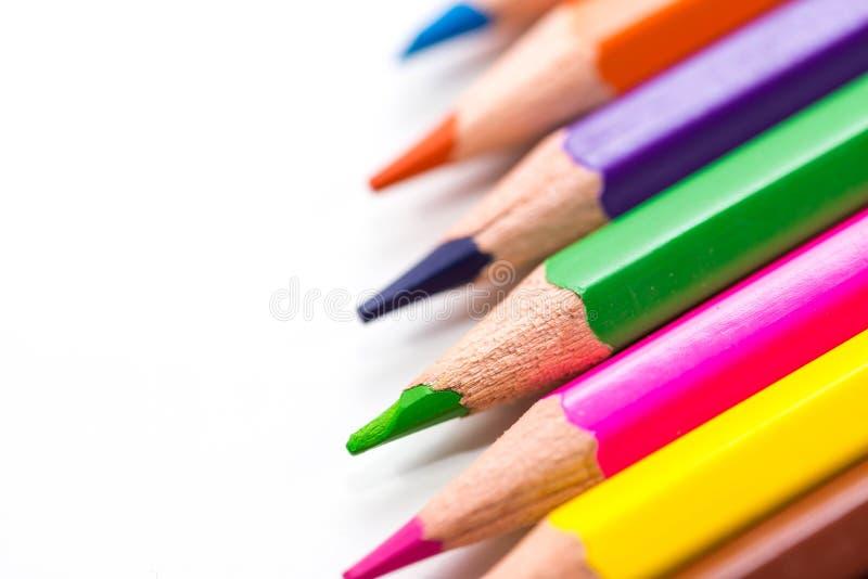 Lápices del color en fila cercanos encima de tiro macro en el fondo blanco fotografía de archivo