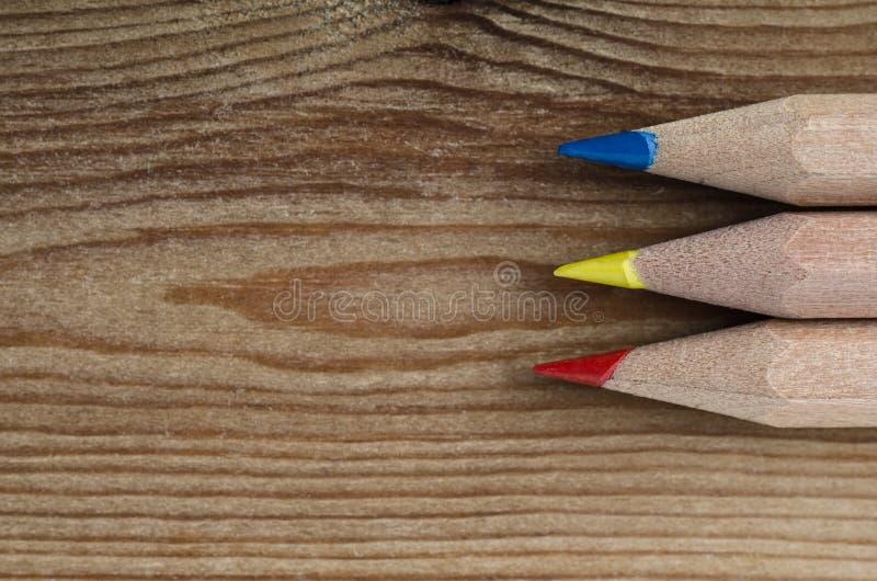 Lápices en colores primarios en la madera fotografía de archivo libre de regalías