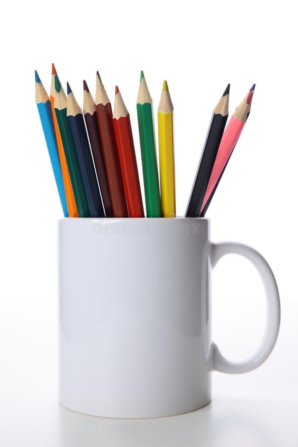 Lápices en la taza blanca imagen de archivo