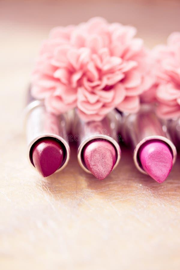 Lápices labiales del encanto y pétalos de la flor imágenes de archivo libres de regalías