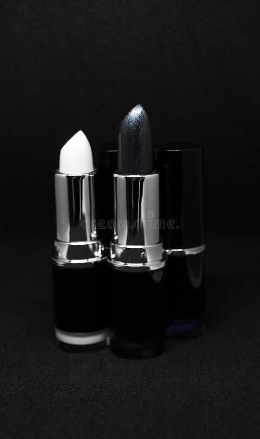 Lápices labiales en fondo negro imagenes de archivo