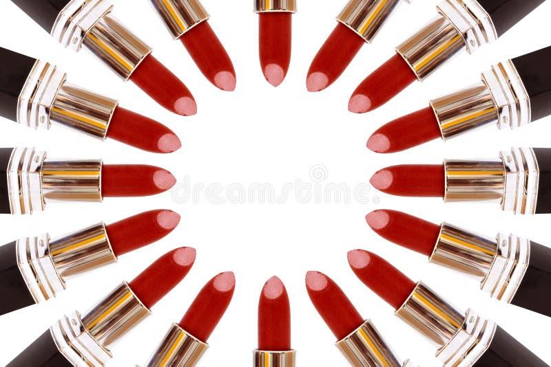 Lápices labiales rojos que hacen un círculo en el fondo blanco imagen de archivo libre de regalías