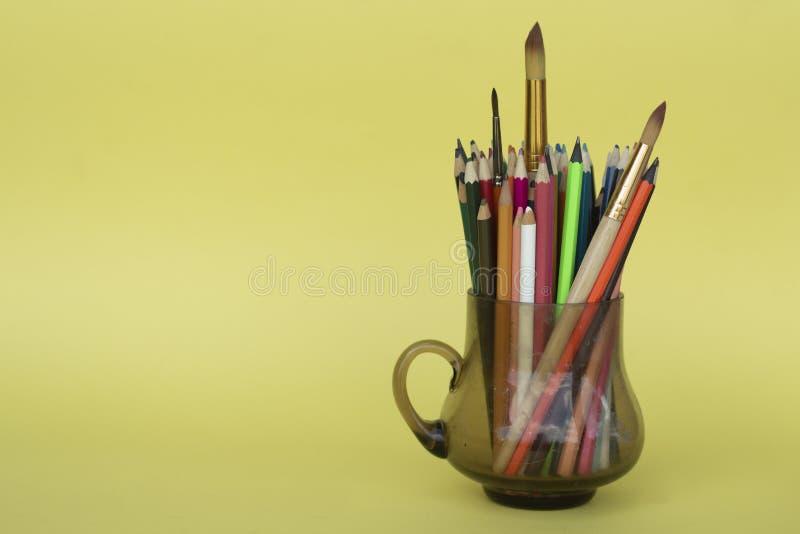 Lápices multicolores en una taza de cristal transparente aislada en amarillo Creatividad de los ni?os imagenes de archivo