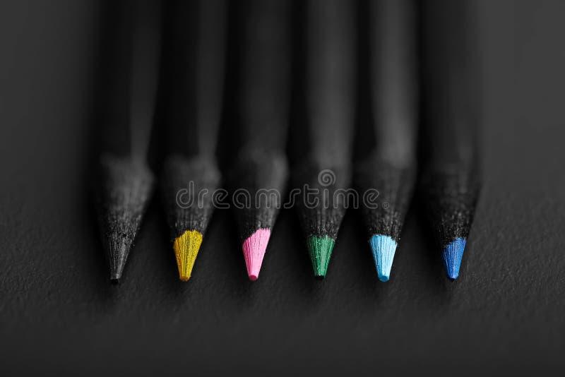 Lápices negros, coloreados, en fondo negro, profundidad baja del fi fotos de archivo libres de regalías