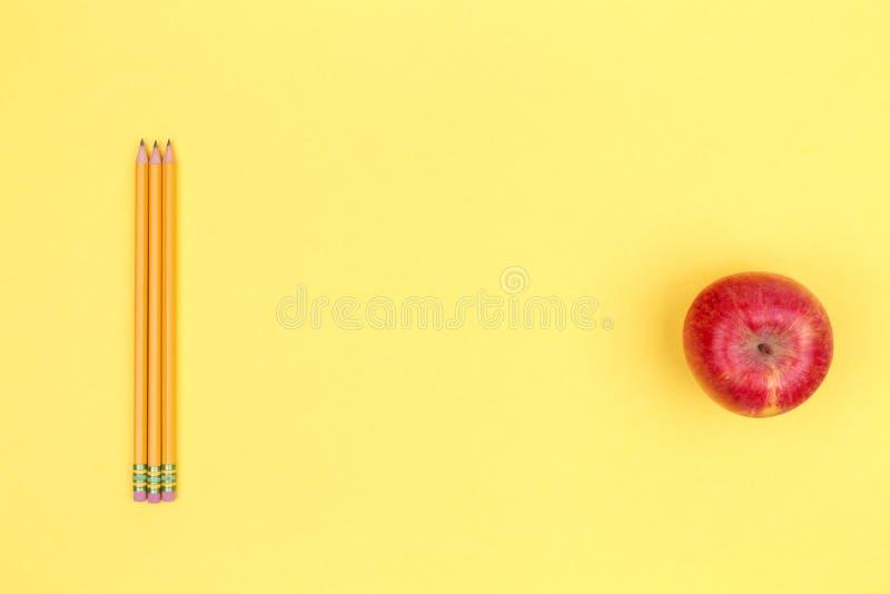 Lápices y manzana en un fondo amarillo De nuevo a concepto de la escuela fotos de archivo libres de regalías