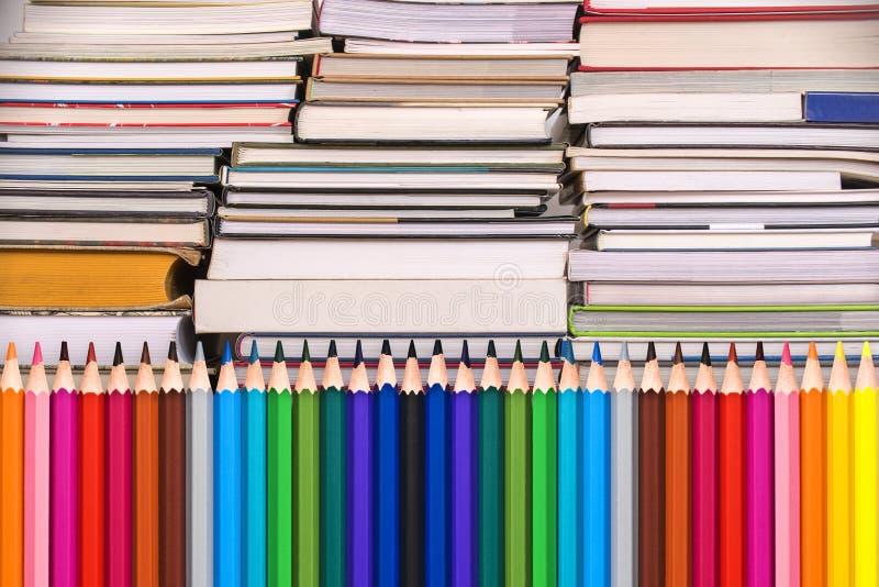 Lápices y pilas de madera coloridos de libros, de nuevo a concepto de la escuela fotos de archivo