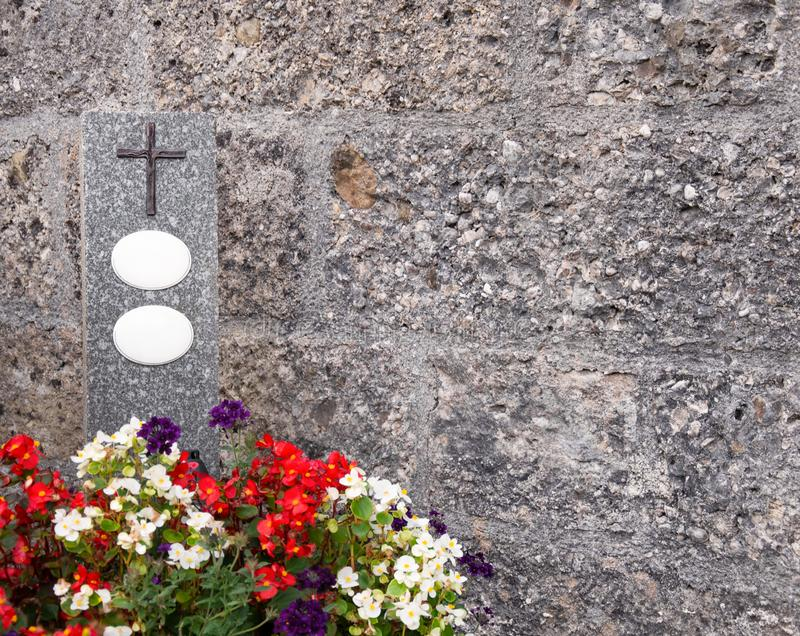 Lápida mortuaria con las placas cruzadas y vacías rodeadas por las begonias foto de archivo libre de regalías