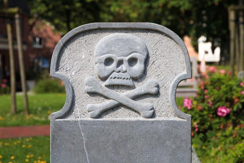 Lápida mortuaria en blanco con el cráneo y la bandera pirata foto de archivo