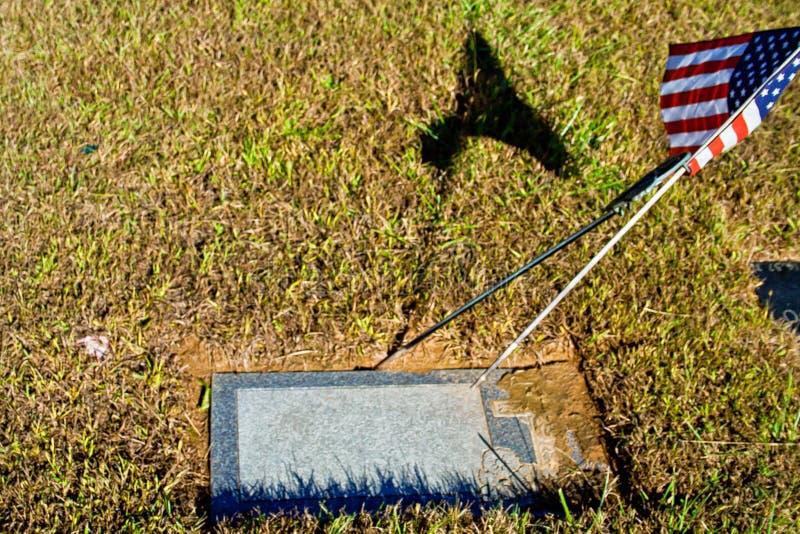Lápida mortuaria en blanco con la bandera americana imagen de archivo