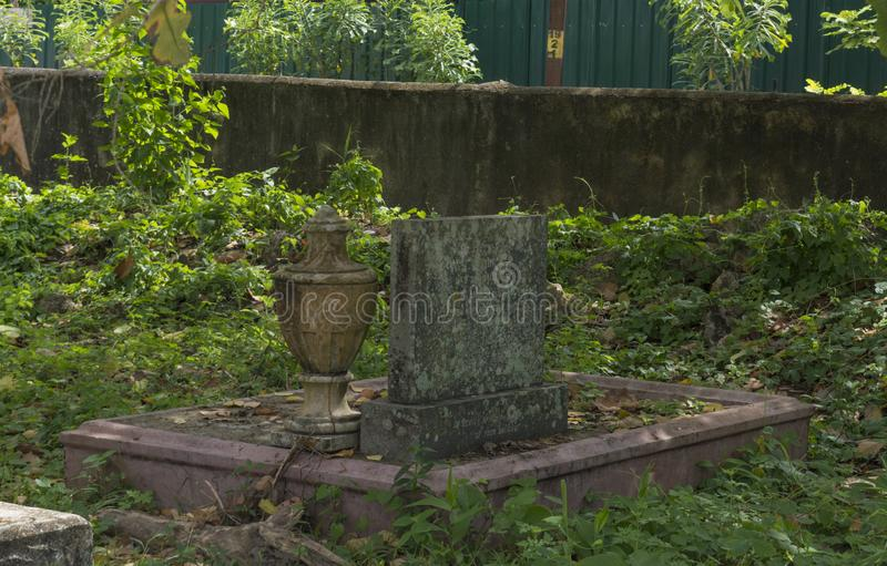 L?pida mortuaria y urna en el cementerio antiguo viejo cerca del templo budista en Weligama foto de archivo libre de regalías
