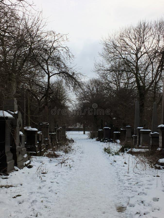 Lápidas mortuarias nevadas a lo largo de una trayectoria en el carril anterior del woodhouse cemetrary en Leeds ahora un parque foto de archivo
