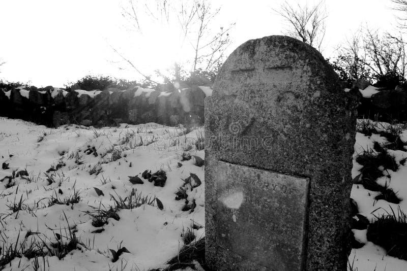 Lápide velha no churchyard nevado fotografia de stock