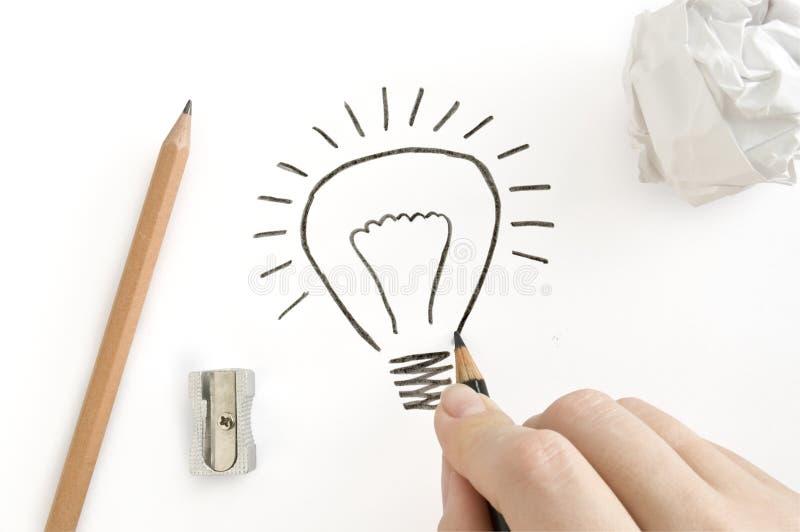 Lápis à disposicão e lâmpada do desenho foto de stock royalty free