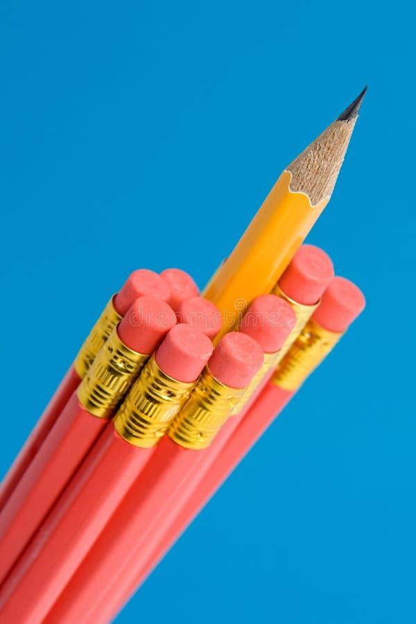 Lápis amarelo afiado entre lápis vermelhos fotografia de stock royalty free