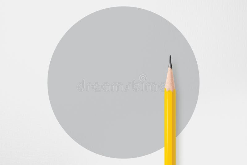 Lápis amarelo com círculo cinzento fotografia de stock