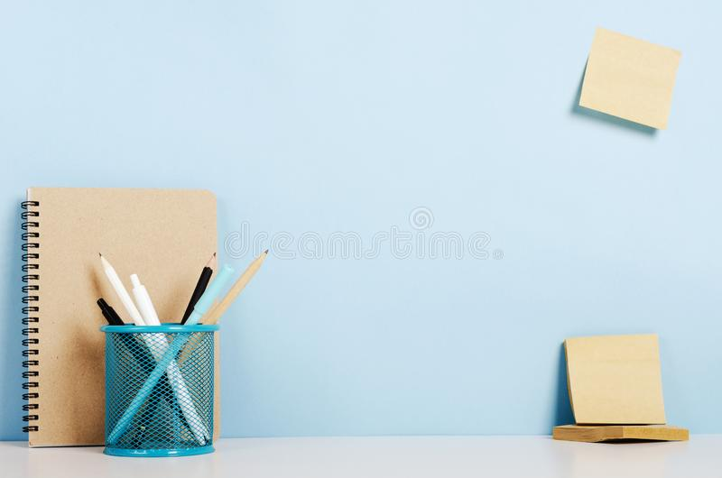 Lápis azuis, brancos e pretos, penas no suporte, caderno em uma tabela branca, etiquetas do ofício na parede do pombo, escritório imagem de stock