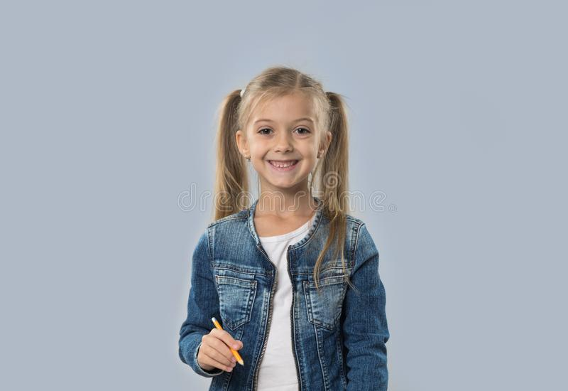 Lápis bonito da posse da menina que escreve o revestimento de sorriso feliz das calças de brim do desgaste isolado fotos de stock