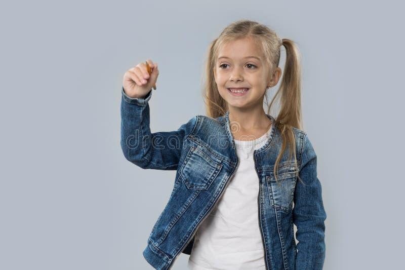Lápis bonito da posse da menina que escreve o revestimento de sorriso feliz das calças de brim do desgaste isolado fotografia de stock