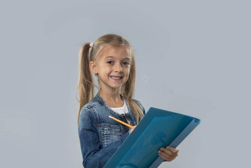 Lápis bonito da posse da menina que escreve o revestimento de sorriso feliz das calças de brim do desgaste isolado imagem de stock