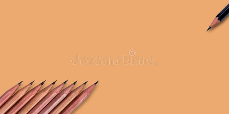 lápis castanhos colocados sobre um fundo de papel cor laranja pálido, cor de laranja, com espaço de cópia para a sua imagem ou te fotografia de stock royalty free