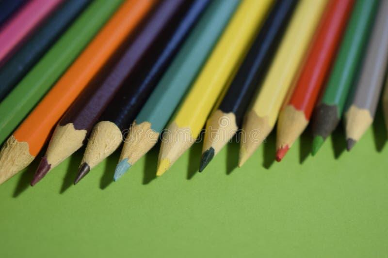 Lápis colorido do close up no fundo de papel verde foto de stock royalty free