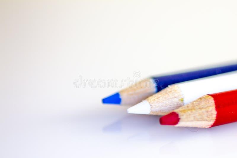 Lápis coloridos brancos e azuis vermelhos no fundo branco foto de stock royalty free