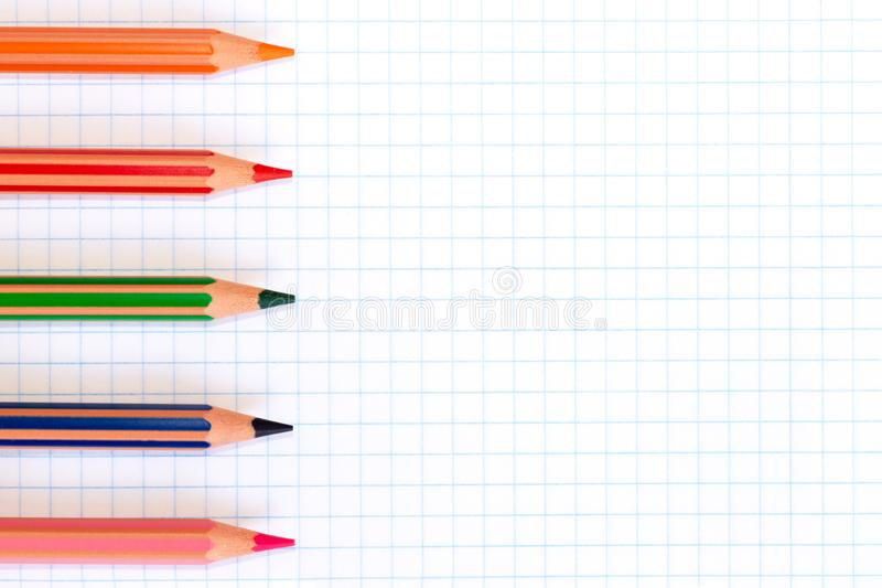 Lápis coloridos de cores vermelhas, verdes, alaranjadas, cor-de-rosa e azuis em um papel quadriculado do livro de exercício com e imagens de stock