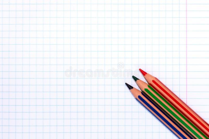 Lápis coloridos de cores vermelhas, verdes e azuis em um papel quadriculado do livro de exercício com espaço da cópia fotografia de stock