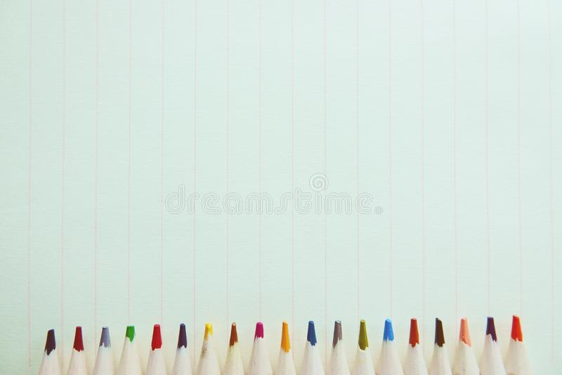 Lápis coloridos de madeira em um fundo do papel do caderno imagem de stock