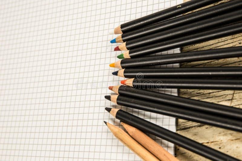 Lápis coloridos e papel esquadrado, retorno às maneiras velhas de desenho e conceito colorindo fotografia de stock royalty free